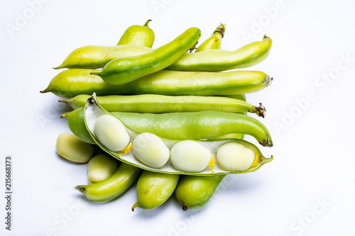 New harvest of healthy vegetables, green fresh raw big broad beans close up isolated on white background