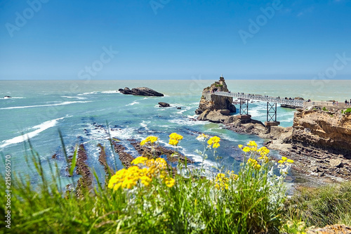 Biarritz city and view of its the famous landmark Rocher de la Vierge, a statue of Virgin Mary on the rock. Bay of Biscay, Atlantic coast, Basque country, France. Summer sunny day
