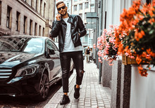 Fashionable Guy In Sunglasses Dressed In A Black Leather Jacket And Jeans Talks By A Smartphone While Standing Near A Luxury Car On Old Europe Street.