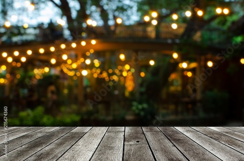 Photo sur Aluminium Jardin empty modern wooden terrace with abstract night light bokeh of night festival in garden, copy space for display of product or object presentation, vintage color tone