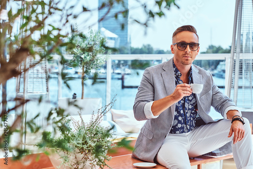 Obraz Confident successful man with stylish hair dressed in modern elegant clothes holds cup of coffee while sitting on a table at outdoor cafe against the background of city wharf. - fototapety do salonu