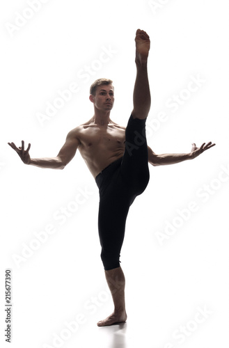 front view, one young man, ballet dancer, standing on one leg, other leg in high in mid-air, white background. arms outstretched. Wall mural
