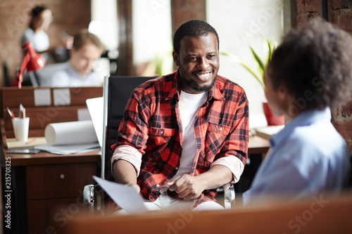 Obraz Smiling African businessman in casual clothes conducting the interview with woman at office - fototapety do salonu