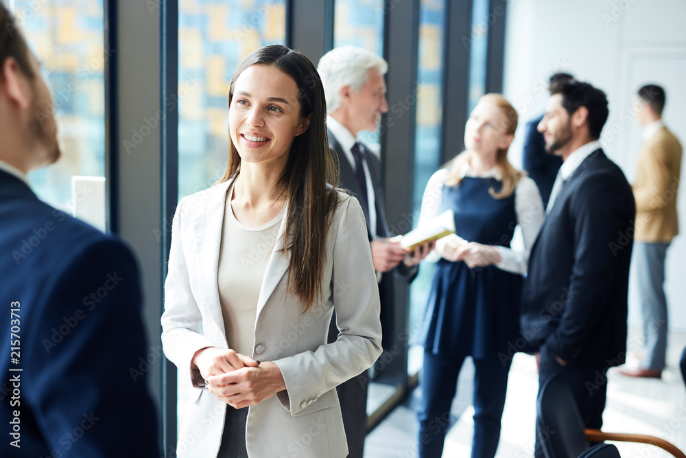 Fototapety, obrazy: Smiling pretty young business lady in jacket talking to colleague and discussing business forum topics during break