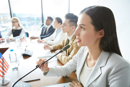 Tablou Canvas Serious confident attractive female politician speaking into microphone and ampl