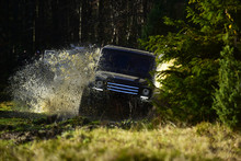 Rallying, Competition And Four Wheel Drive Concept. Motor Racing In Autumn Forest. Sport Utility Vehicle Or SUV Crossing Puddle With Splash. Offroad Race On Fall Nature Background.