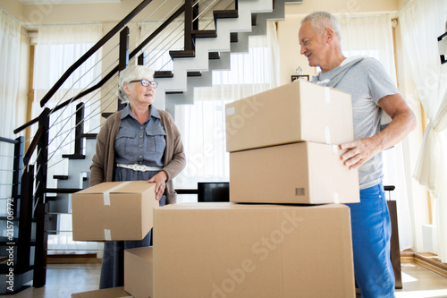 Portrait of happy senior couple packing cardboard boxes while moving to new hous Fototapet