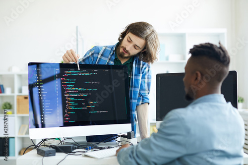 Fototapeta Confident professional multiethnic coders discussing programming language: hipster young man pointing at screen and explaining programming algorithm obraz