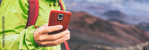 Fototapeta Mobile phone man using his cellphone texting a text message during hiking travel abroad in nature mountains, banner panorama. obraz