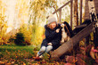canvas print picture autumn portrait of happy kid girl playing with her spaniel dog in the garden, sitting on wooden stairs and hugs