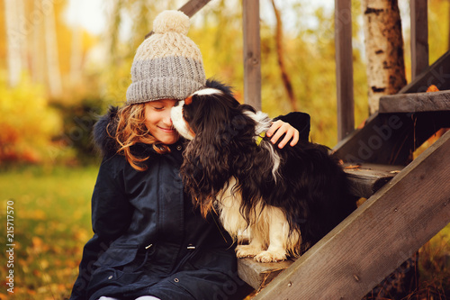 canvas print motiv - mashiki : autumn portrait of happy kid girl playing with her spaniel dog in the garden, sitting on wooden stairs and hugs
