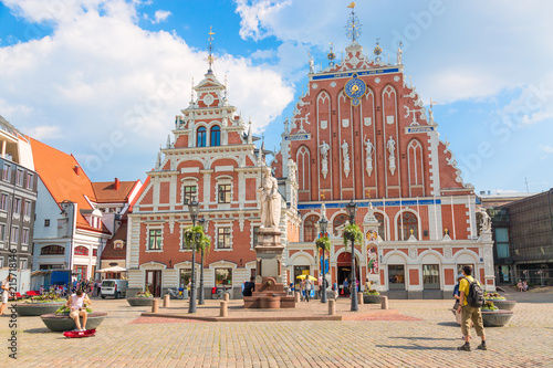 Fotografie, Obraz View of the Old Town square, Roland Statue, The Blackheads House near St Peters Cathedral against blue sky in Riga, Latvia