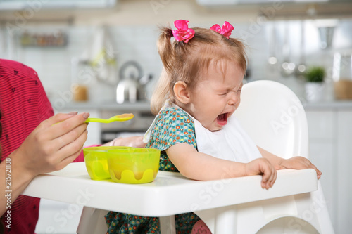 Photo Mother feeding her little baby with healthy food in kitchen