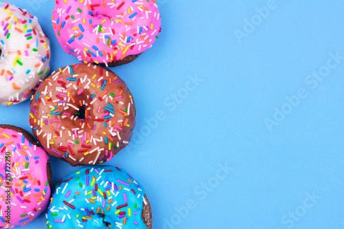 Side border of assorted donuts with frosting and sprinkles against a pastel blue background