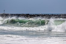 Waves Crashing On The Shore With A Rock Jetty In The Background