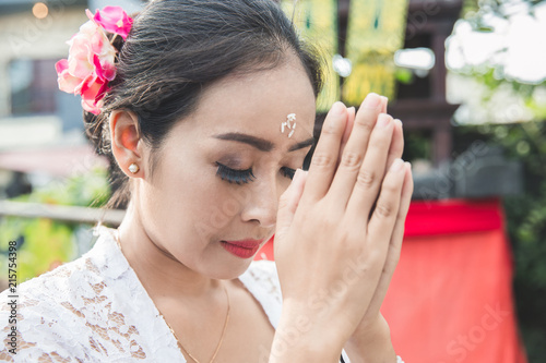 Foto op Plexiglas Bedehuis balinese woman praying at temple on small shrines in houses