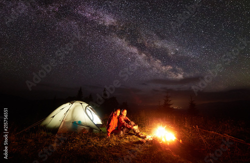 Türaufkleber Braun Night camping in mountains. Couple hikers, man and woman having a rest near burning campfire and illuminated tent under beautiful evening starry sky and Milky way on distant hills background.