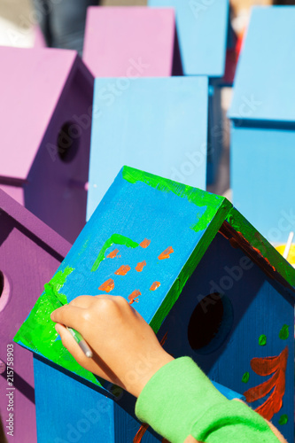 Canvas-taulu Child hand painting a birdhouse bright colors of blue and purple