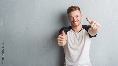 Fotografie, Obraz  Young redhead man over grey grunge wall approving doing positive gesture with hand, thumbs up smiling and happy for success