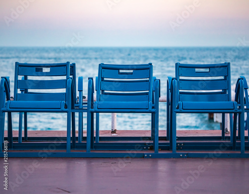 Fototapeta Mediterranean Sea and famous blue chais on Promenade des Anglais at sunset in Ni