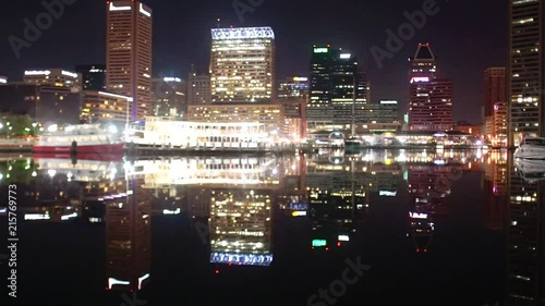 Fotografering  The skyline and docks reflecting in the water at night