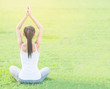 Young lady doing yoga exercise in green field outdoor area showing calm peaceful in meditation mind - people practise yoga for meditation and exercise concept