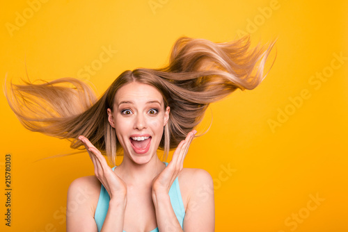 Fotografie, Obraz  Portrait of cute straight-haired blonde caucasian smiling girl, wearing casual blue shirt, amazed, showing excitement, wind blows hair
