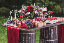 Wedding Reception Wooden Table Standing On Two Barrels, Decorated With Red Flowers, Sweets, Drinks And Silk. Rustic Style