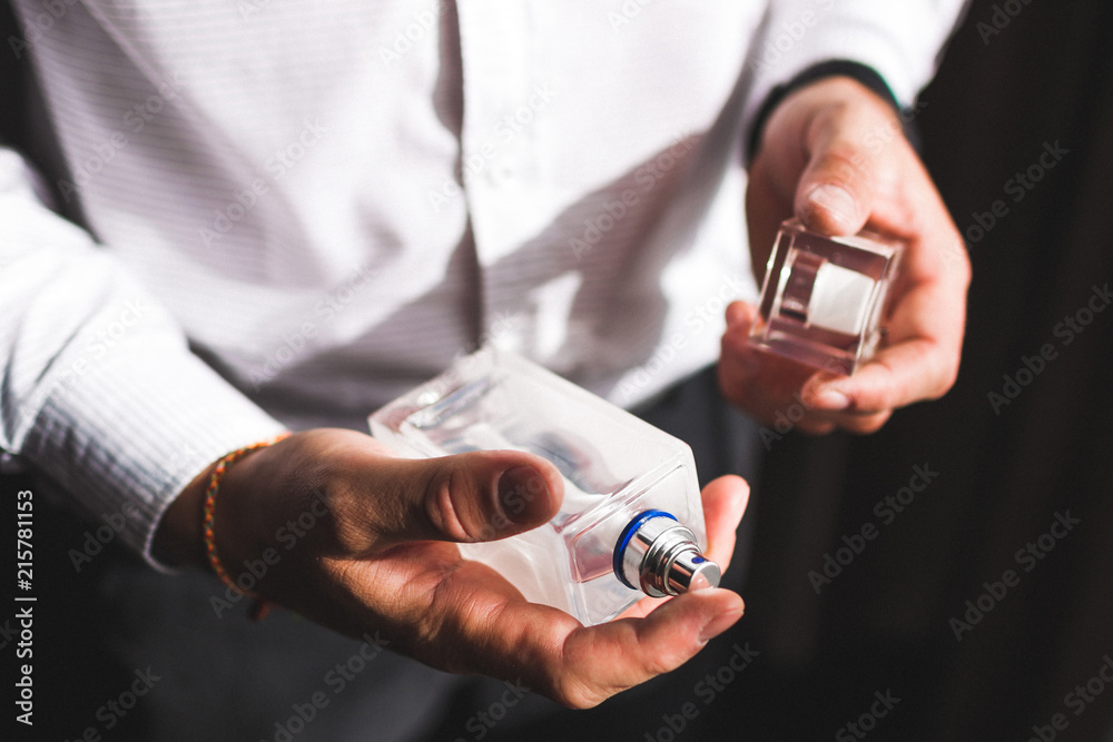 Fototapety, obrazy: Man holding bottle of perfume and smells fragrance