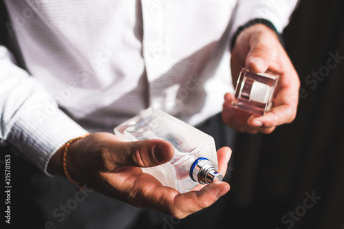 Fototapeta Man holding bottle of perfume and smells fragrance obraz