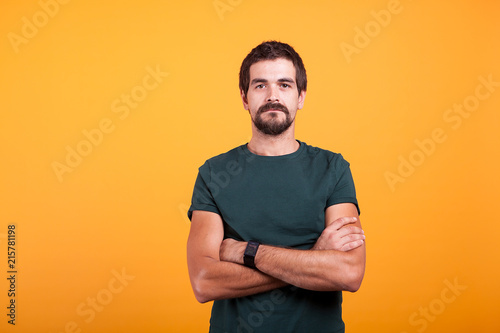 Serious man isolated on orange background. Confident person looking in the camera