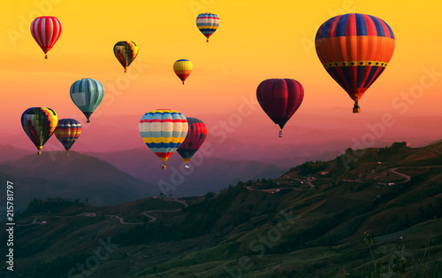 Poster Balloon Hot Air balloons flying over road in forest landscape sunset background.