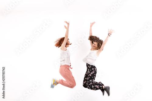 Fototapeta Two happy and positive women jump over a white wall in studio obraz na płótnie