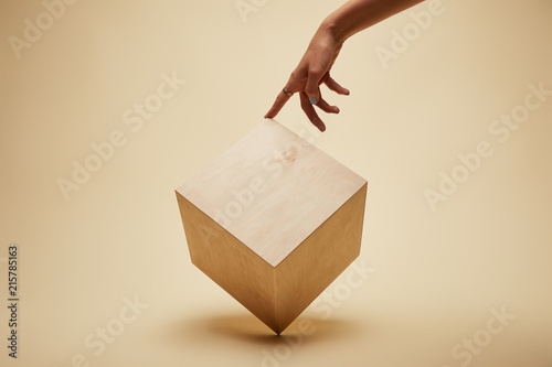 Fotografia  cropped image of woman touching wooden cube on beige