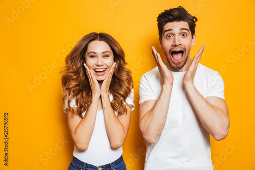 Photo of amazed couple man and woman in basic clothing screaming in surprise or Slika na platnu