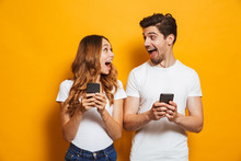 Photo Of Positive Excited People Man And Woman Screaming And Looking At Each Other While Both Using Mobile Phones, Isolated Over Yellow Background