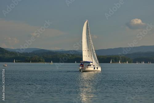Photo  Jacht na jeziorze, na wodzie błyszczące refleksy - odbicie żaglówki, w tle wiele