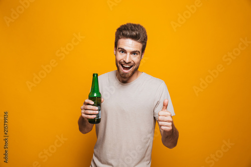 Portrait of a cheerful young man holding beer bottle Canvas Print