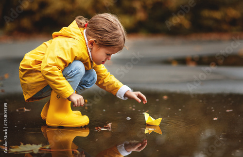 happy child girl with umbrella and paper boat in puddle in autumn on nature.