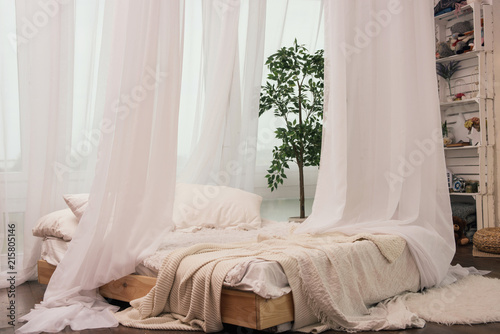 Cozy bed near window with beautiful curtains in room Fototapeta