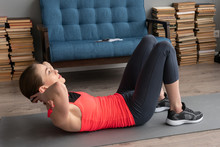 Fitness Woman Doing Abs Crunch Exercise On Floor At Home