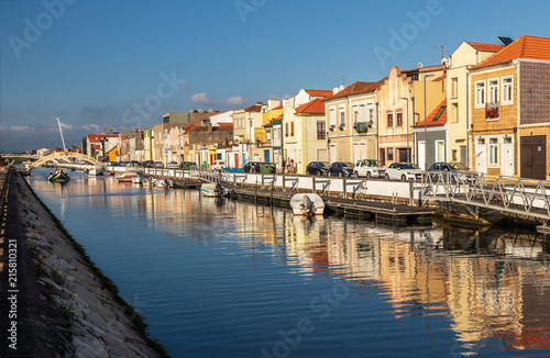 Fotografie, Obraz  Canal de São Roque in the city of Aveiro, Portugal, flanked by colorful houses, boats anchored and in the background a moliceiro to pass under the bridge of Carcavelos