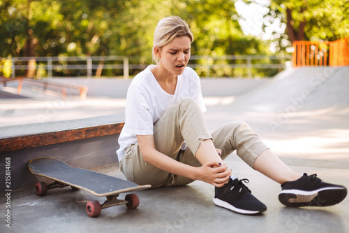 Fotografía  Upset skater girl holding her painful leg with skateboard near while spending ti