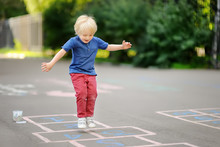 Child Playing Hopscotch On Pla...