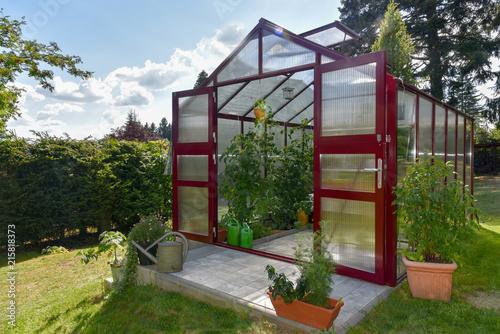 Ein rotes Gewächshaus im Garten Fototapet