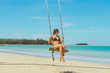 Swinging sexy girl at the beach n front of the tropical sea