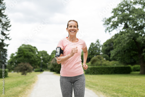 Foto fitness, sport and healthy lifestyle concept - smiling woman with earphones wear