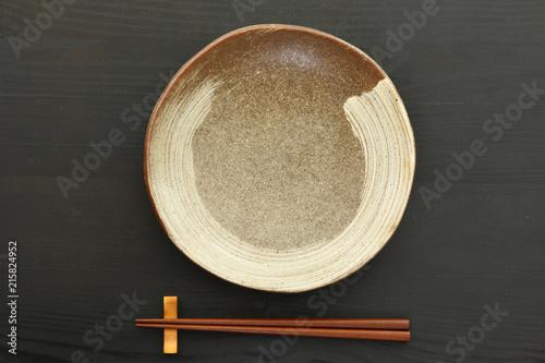 黒いテーブルに置かれた土製の皿と箸