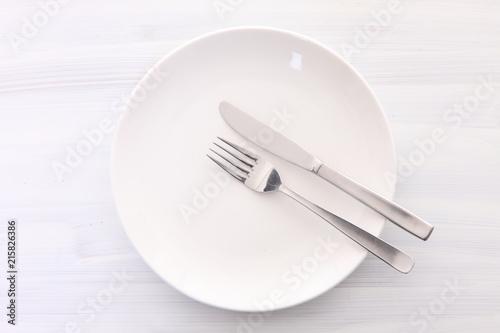 Fotografía  白い木製テーブルに置かれた白い皿とカトラリーによる食事終了の合図