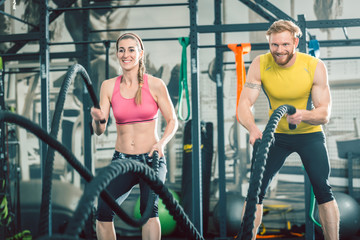 Low-angle view of a strong and competitive couple smiling while exercising together with battle ropes during functional training at the gym
